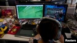 """Seorang pekerja mengamati komputer yang menampilkan video game """"Glorious Mission Online"""" di sebuah perusahaan pembuat game di Shanghai, China. (Foto: Reuters/ Aly Song)"""