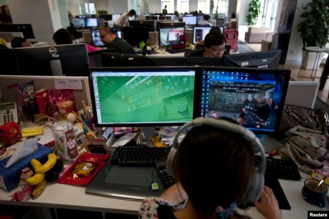 """资料照:中国电游开发公司的员工观看屏幕上显示的电游""""光荣使命""""。(2013年8月2日)"""