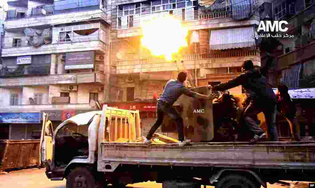 This citizen journalism image provided by the Aleppo Media Center (AMC), an anti-Bashar Assad group, shows Syrian rebels firing an anti-aircraft gun at Syrian airplanes in Aleppo, Feb. 1, 2014.