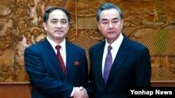 중국 정부 초청으로 지난 3월 방중한 북한 리길성 외무성 부상(왼쪽)이 왕이 중국 외교부장과 만나 악수하고 있다.