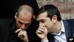 ນາຍົກລັດຖະມົນຕີກຣີສ ທ່ານ Alexis Tsipras (ຂວາ) ໂອ້ລົມກັບ ລັດຖະມົນຕີການເງິນຂອງກຣີສ ທ່ານ Yanis Varoufakis ໃນລະຫວ່າງການອອກສຽງເລືອກຕັ້ງ ປະທານາທິບໍດີ ໃນ Athens, ວັນທີ 18 ກຸມພາ 2015.