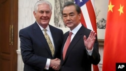 Chinese Foreign Minister Wang Yi gestures while shaking hands with U.S. Secretary of State Rex Tillerson before a bilateral meeting at the Diaoyutai State Guesthouse in Beijing, China, March 18, 2017.