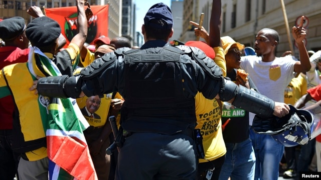 FILE - A police officer tries to control ANC supporters as they attempt to confront members of the opposition Democratic Alliance party marching in central Johannesburg, February  2014.