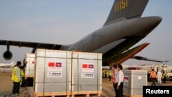 Workers stand next to the shipment of 600,000 doses of the coronavirus disease (COVID-19) vaccines donated by China at the Phnom Penh International Airport, in Phnom Penh, Cambodia February 7, 2021. (REUTERS/Cindy Liu)