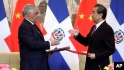 Los ministros de Relaciones Exteriores de República Dominicana, Miguel Vargas, y de China, Wang Yi, se estrechan la mano luego de firmar un comunicado conjunto en Pekín.