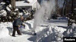 Ông Frank Courtell dọn dẹp tuyết khỏi đường dẫn vào nhà ở Annandale, ngoại ô thủ đô Washington, hôm 24/1.