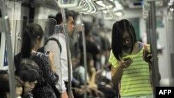 Penumpang kereta bawah tanah di Singapura asyik dengan ponsel pintar mereka (30/4). (AFP / Roslan Rahman)