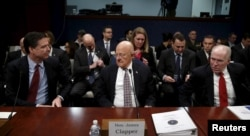 Then-FBI Director James Comey (L), then-U.S. Director of National Intelligence James Clapper (C) and then-CIA Director John Brennan (R) take their seats to testify at a hearing on Capitol Hill in Washington, Feb. 25, 2016.