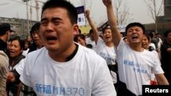 សមាជិកគ្រួសារអ្នកដំណើរលើយន្តហោះម៉ាឡេស៊ី MH370 យំនៅពេលស្រែកពាក្យស្លោកក្នុងអំឡុងពេលតវ៉ានៅមុខស្ថានទូតម៉ាឡេស៊ីនៅទីក្រុងប៉េកាំង កាលពីថ្ងៃអង្គារទី២៥ ខែមីនា ឆ្នាំ២០១៤។
