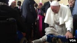 Paus menyapa seorang anak di kursi roda dalam kunjungan ke daerah kumuh Kangemi di Nairobi, Kenya (27/11). (VOA/J. Craig)