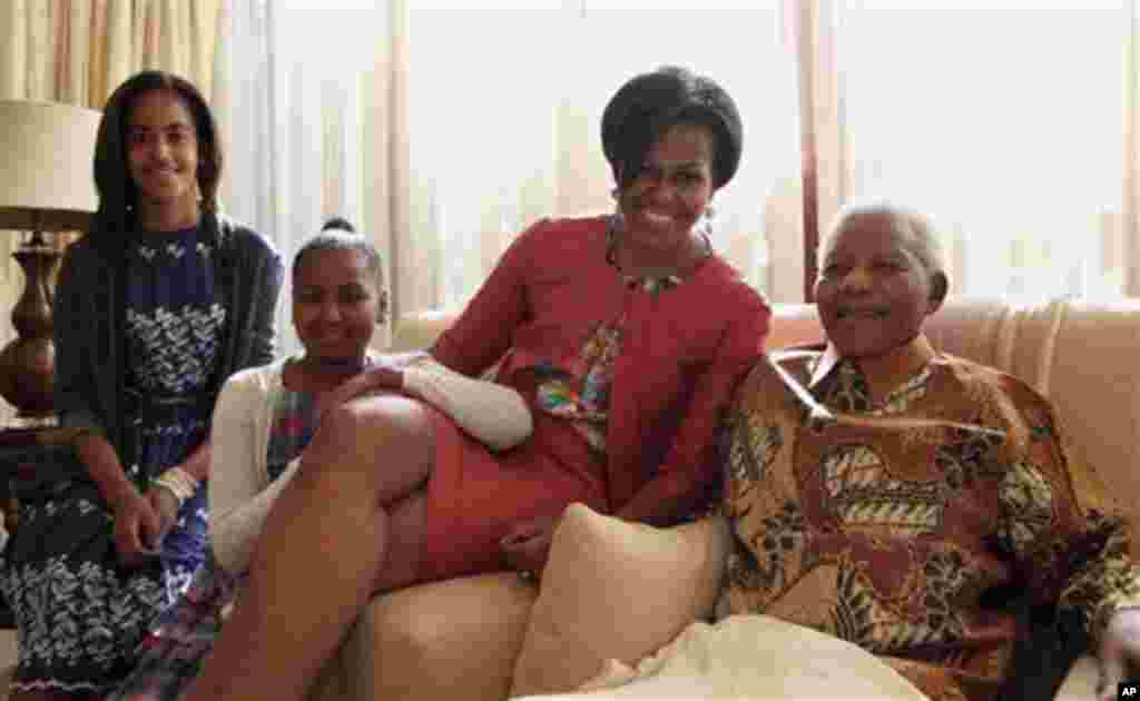 Primeira Dama, Michele Obama, com Nelson Mandela durante a sua visita à África do Sul, em Junho de 2011. As filhas do casal Obama, Malia (esq) e Sasha, acompanharam a mãe.