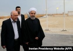 A handout picture released by the official website of the Iranian President Hassan Rouhani shows him (R) walking with Oil Minister Bijan Namdar Zanaganeh (L) at phase 12 of the South Pars gas field facilities in the southern Iranian port of Assaluyeh, on