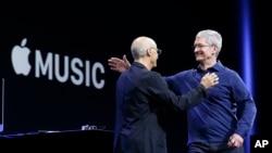 CEO Apple Tim Cook (kanan) merangkul salah satu pendiri Beats by Dre dan pegawai Apple, produser musik Jimmy Iovine dalam sebuah konferensi Apple di San Francisco, Juni 2015. (AP/Jeff Chiu)