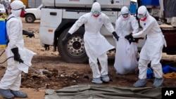 Trabajadores disponen de un cuerpo posiblemente infectado con ébola en Liberia.