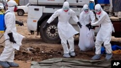 Petugas kesehatan membawa mayat yang ditemukan di jalan yang diduga meninggal akibat virus ebola di Monrovia, Liberia, 12/8/2014.