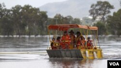 Sebuah kapal kecil darurat membantu warga pindah dari lokasi banjir di kota Rockhampton ke kota Capricorn, Queensland.
