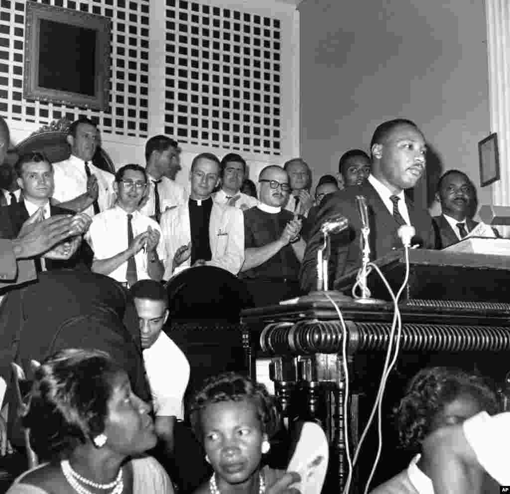 A group of clergymen from the northern states applaud Southern Christian Leadership Conference president Martin Luther King Jr. as he speaks at a church in Albany, Georgia, August 28, 1962.