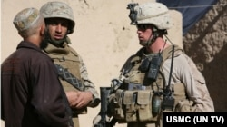 一名美國海軍陸戰隊下士在翻譯的幫助下在阿富汗某鎮與一名村民交談。(2009年12月6日)
