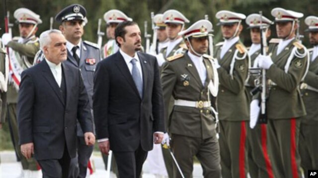 Lebanese Prime Minister Saad Hariri, center left, reviews an honor guard as he is accompanied by Iranian Vice-President Mohammad Reza Rahim, left, during an official welcoming ceremony, in Tehran, Iran, 27 Nov 2010