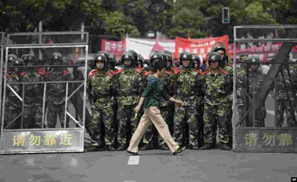 A woman walks past paramilitary police officers standing guard during anti-Japan protests near the Japanese Consulate General, Shanghai, China, September 18, 2012.