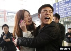 A relative of a passenger onboard Malaysia Airlines flight MH370 cries as she talks on her mobile phone at the Beijing Capital International Airport, China, Mar. 8, 2014.