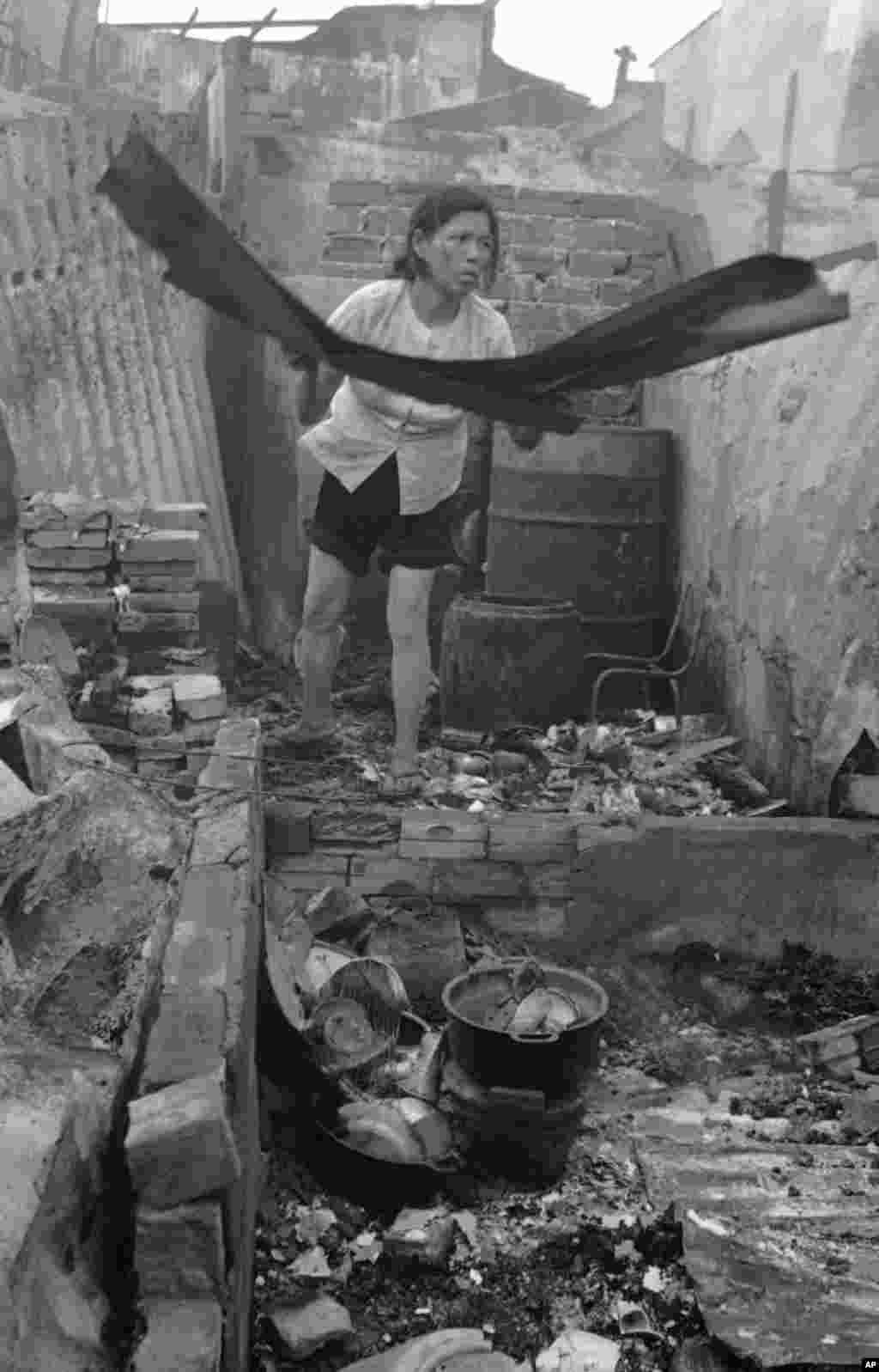 Một người phụ nữ thu nhặt những gì còn sót lại của căn nhà bà sau vụ tấn công bằng rocket vào Sài Gòn gây hỏa hoạn, ngày 27 tháng 4, 1975. Hãng tin AP cho biết những rocket là do Nga chế tạo được quân Cộng sản miền Bắc bắn từ ngoài thành phố.