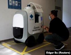 Seorang pelanggan mengambil belanjaannya yang diantar oleh robot Camello di Singapura, 6 April 2021. (Foto: Edgar Su/Reuters)