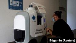 Seorang pelanggan mengambil belanjaannya yang diantar oleh Camello, robot otonom pengantar belanja, di Singapura, 6 April 2021. (Foto: Edgar Su/Reuters)