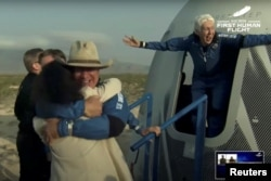 Billionaire entrepreneur Jeff Bezos and aviator Wally Funk, exit the capsule after the world's first pilotless suborbital flight on a New Shepard Blue Origin rocket, lands near Van Horn, Texas, USA, July 20, 2021. (REUTERS)