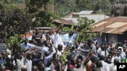 Leader of the opposition party Forum for Democratic Change Kizza Besigye, background center right, beside his wife Winnie Byayima, left, waves to large crowds of supporters as he returns from Nairobi after medical treatment.