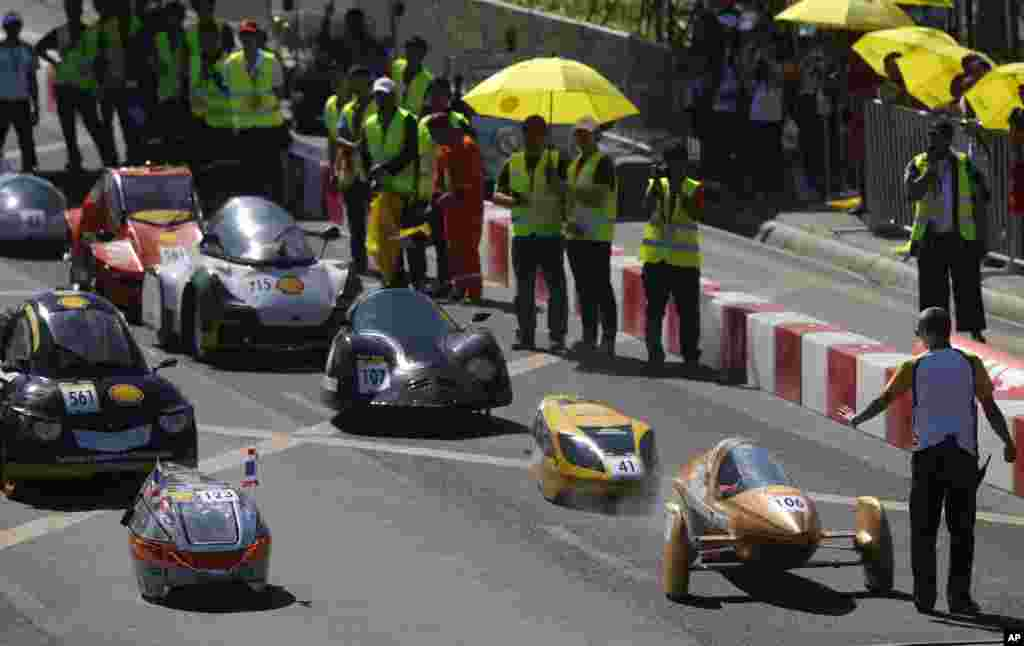 """Student-participants from Asian countries prepare to race their hand-made fuel-efficient vehicles during the competition dubbed Shell Eco-Marathon (SEM) Asia in Manila, Philippines. Organizers said the race has attracted 109 students from 15 countries in Asia and the Middle East and is aimed to """" showcase their innovations in sustainable mobility."""""""