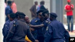 In this Thursday, Sept. 1, 2011 photo, an unidentified journalist from an opposition television station is detained and roughed up by police while covering an opposition protest in Kinshasa, Congo. Minutes after this picture was taken, the photographer wh
