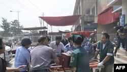 Hình ảnh cho thấy nhân viên cứu hộ khiêng một nạn nhân bị thương sau vụ tấn công ra khỏi trạm cảnh sát ở thành phố Hotan ở miền nam Tân Cương, ngày 18/7/2011