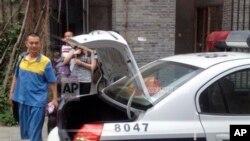 Seniman Australia kelahiran China, Guo Jian (kiri), mengenakan seragam tahanan berjalan menuju mobil polisi setelah mengemasi beberapa barang-barang dari studionya di Beijing (6/6).