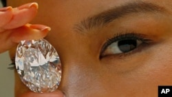 The 118.28-carat white diamond is displayed by a model at a press preview at Sotheby's auction house, Thursday, Sept. 19, 2013.