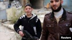 Seorang pejuang muda dari laskar pemberontak Suriah tengah bersiap dengan senjatanya di wilayah Haresta, Damaskus (Foto: dok).
