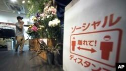 Shinichiro Hirano berjalan di tokonya, Sun Flower Shop, di mana dia memasang peringatan agar pelanggan menjaga jarak aman, di tengah pandemi virus corona, 22 Juni 2020, di Tokyo. (Foto: AP)