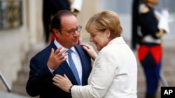 French President Francois Hollande, left, greets German Chancellor Angela Merkel prior to their meeting at the Elysee Palace in Paris, Thursday, Sept. 15, 2016.