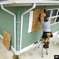 Ismael Ramirez et son frère Jorge Ramirez clouent des contreplaqués sur les fenêtres d'une maison