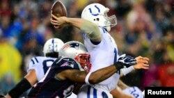 El quarteback de los Colts de Indianápólis, Andrew Luck, lanzará el ovoide pese a ser atrapado por Jamie Collins de los Patriotas de Nueva Inglaterra. [Foto: Andrew Weber-USA TODAY Sports].