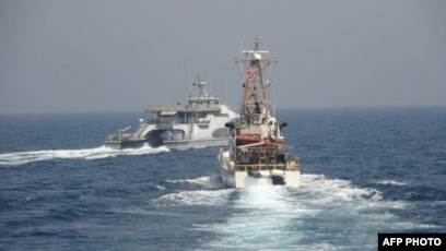 Kapal Angkatan Laut Iran (IRGCN) Harth 55 (kiri) melintasi haluan kapal patroli Coast Guard USCGC Monomoy (WPB 1326) (kanan) saat sedang melakukan patroli keamanan maritim rutin di perairan internasional Teluk Arab selatan, 2 April 2021. (Foto: Angkatan Laut AS/AFP)