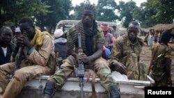 FILE - Seleka fighters sit on a pick-up truck in the town of Goya, Central African Republic, June 11, 2014. UPC rebels, a Seleka offshoot, are being blamed for the current surge in violence in Basse-Kotto, a prefecture in the eastern part of the CAR.