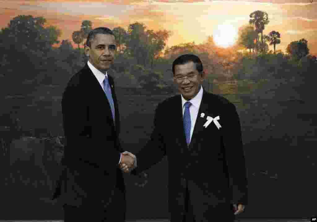 Obama bersama Perdana Menteri Kamboja Hun Sen sebelum pertemuan dengan pemimpin ASEAN di Phnom Penh (19/11).