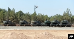 "FILE - Turkish tanks stationed near the Syrian border, in Karkamis, Turkey, Saturday, Sept. 3, 2016. Turkey's state-run news agency says Turkish tanks have entered Syria's Cobanbey district northeast of Aleppo in a ""new phase"" of the Euphrates Shield operation."