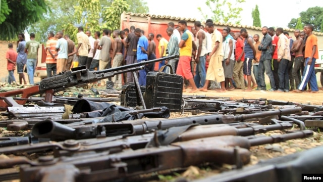 FILE - Suspected fighters are paraded before the media by Burundian police near a recovered cache of weapons after clashes in the capital, Bujumbura, Dec. 12, 2015.