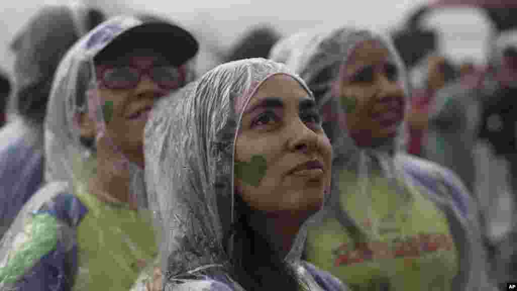 People with a green heart painted on their faces attend the People's Climate March under the rain at Ipanema beach, Rio de Janeiro, Brazil, Sept. 21, 2014.