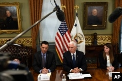 Vice President Mike Pence, center, sitting next to Carlos Anez, left, and Veronica Vadell Weggeman, right, speaks during a meeting in the Vice President's Ceremonial Office on the White House complex in Washington, with family members of the six Citgo executives currently detained in Venezuela, April 2, 2019.