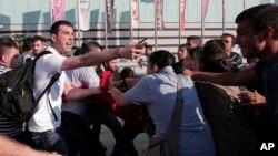 一名土耳其便衣警察(左)阻止伊斯坦布尔的示威者,示威者试图组织游行声讨在苏鲁奇制造的爆炸案(2015年7月21日)