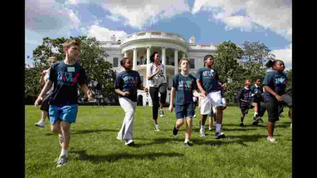 La primera dama Michelle Obama junto a estudiantes locales, en el jardín de la Casa Blanca realziando actividades físicas (25 de mayo de 2010).