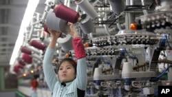 지난 1월 북한 평양양말공장 여성 노동자가 실을 감은 얼레를 기계에 걸고 있다.